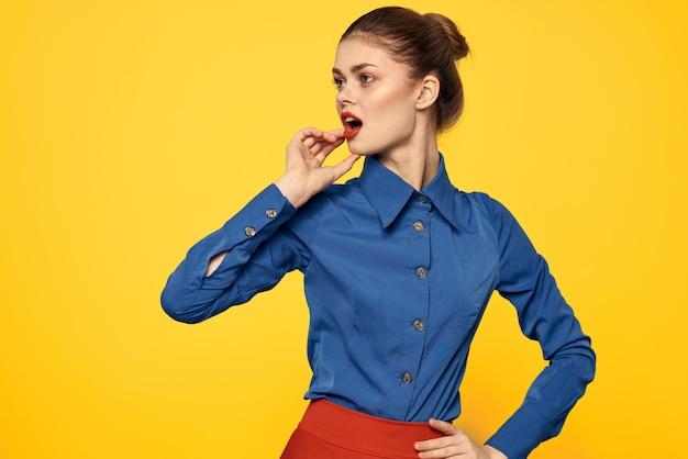 Mulher em uma camisa azul brilhante, saia vermelha, posando em uma parede colorida, imagem elegante de negócios