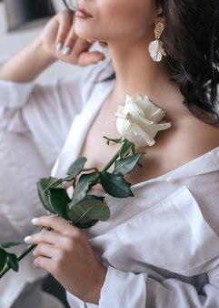 Mulher em uma camisa branca tem uma rosa nas mãos.
