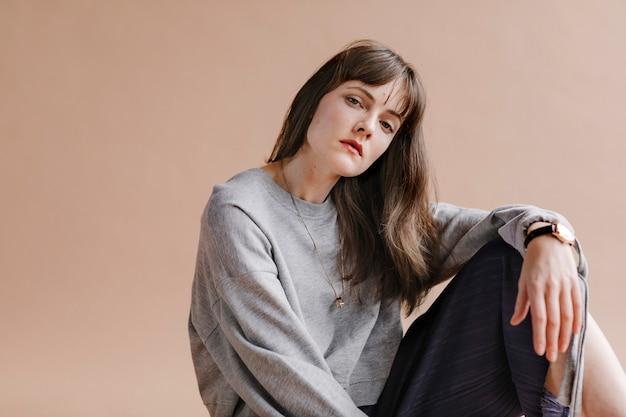 Mulher em uma camisa cinza de manga comprida