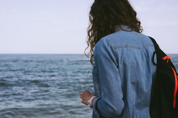 Mulher em uma camisa jeans e uma mochila fica na beira da praia e olha para o mar
