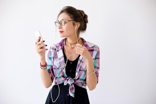 Mulher em uma camisa xadrez em copos plaing com fones de ouvido