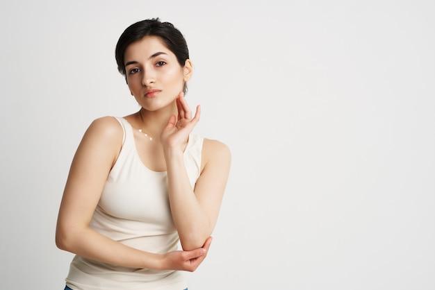 Mulher em uma camiseta branca com creme no corpo cosméticos pele limpa closeup