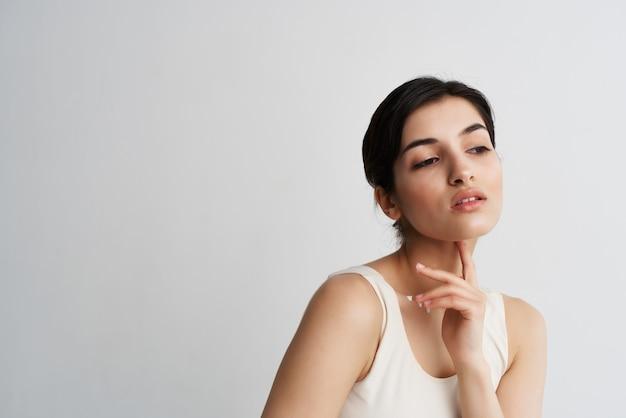 Mulher em uma camiseta branca com loção nas mãos cosméticos pele limpa closeup