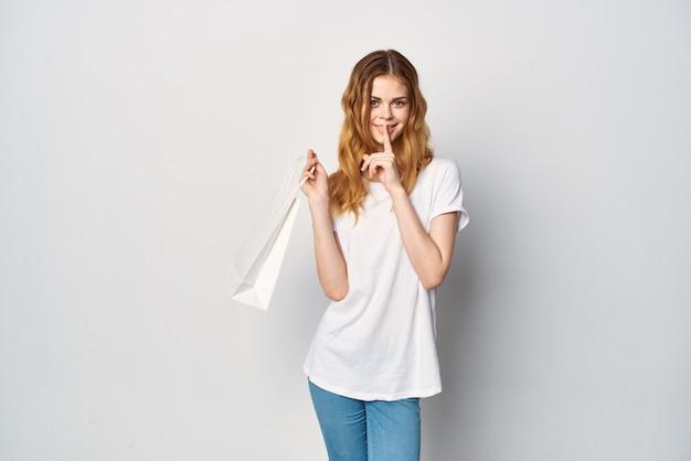 Mulher em uma camiseta branca com um pacote branco nas mãos.