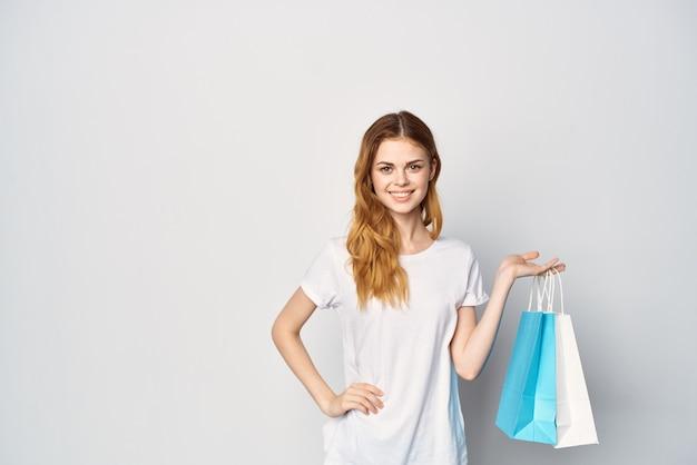 Mulher em uma camiseta branca com um pacote nas mãos um presente de compras de fundo claro