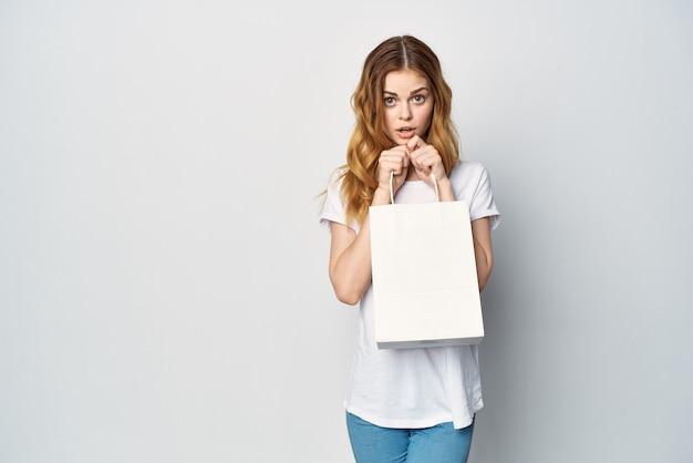 Mulher em uma camiseta branca com um pacote nas mãos um presente de compras luz de fundo