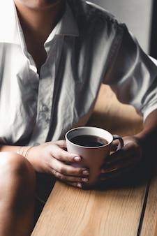 Mulher em uma camiseta branca contém café da manhã em uma xícara de cerâmica rosa. manicure. vista frontal