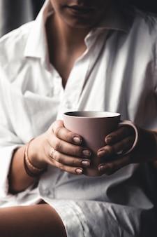 Mulher em uma camiseta branca contém café da manhã em uma xícara de cerâmica rosa.