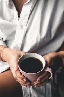 Mulher em uma camiseta branca segura o café da manhã em uma xícara de cerâmica rosa. manicure. vista frontal