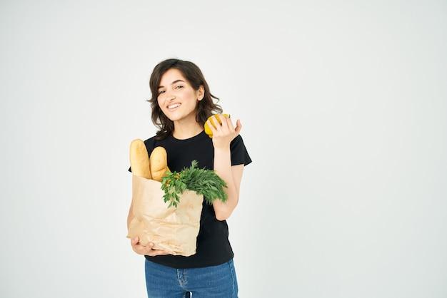 Mulher em uma camiseta preta com um pacote de mantimentos nas mãos de um entregador