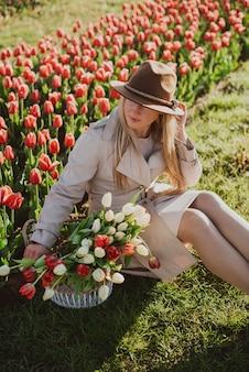Mulher em uma capa de chuva ao nascer do sol entre as linhas de tulipas