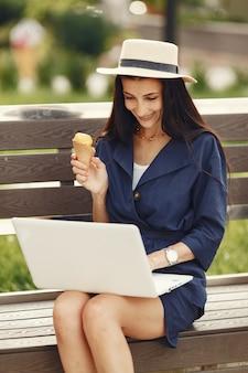 Mulher em uma cidade de primavera. senhora com um laptop. menina sentada em um banco.