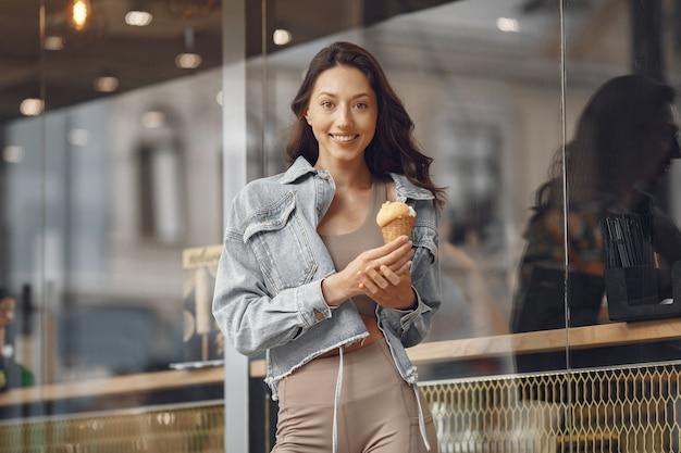 Mulher em uma cidade de verão. senhora com sorvete. morena perto do prédio.
