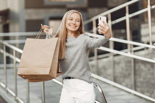 Mulher em uma cidade de verão. senhora com telefone celular. mulher com um suéter cinza.