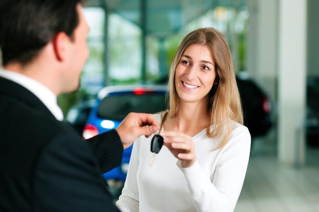Mulher em uma concessionária de carros, comprar um auto, o representante de vendas, dando-lhe a chave