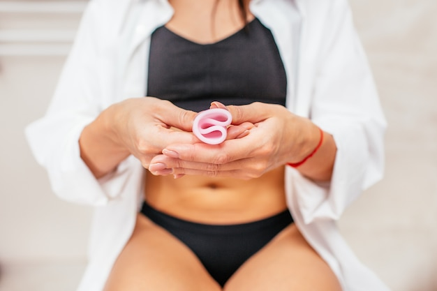 Mulher em uma cueca preta, segurando um copo menstrual rosa na mão, sentado em um vaso sanitário. foco seletivo. outra opção para os períodos da mulher.