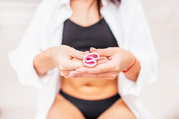 Mulher em uma cueca preta, segurando um copo menstrual rosa na mão