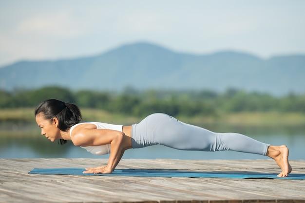 Mulher em uma esteira de ioga para relaxar no parque no lago de montanha. garota atraente e desportiva em roupas esportivas. fazendo flexões ou exercícios de flexões, phalankasana, pose de prancha, garota esportiva malhando.