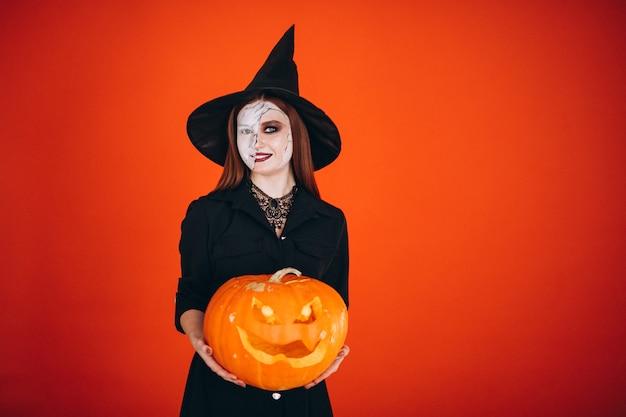 Mulher em uma fantasia de halloween com uma abóbora