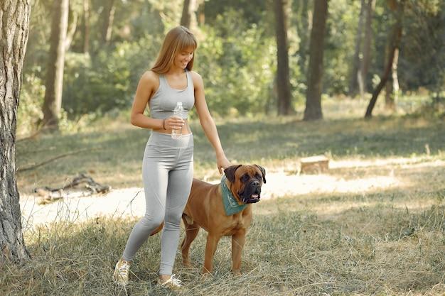 Mulher em uma floresta de verão brincando com cachorro
