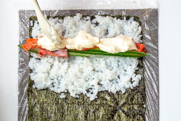 Mulher em uma folha de nori com arroz pepino e peixe colocando queijo macio