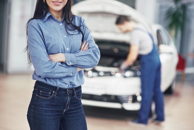 Mulher em uma garagem de carro, recebendo serviço mecânico. o mecânico trabalha sob o capô do carro