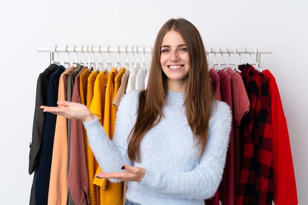 Mulher em uma loja de roupas com muitas roupas para trás