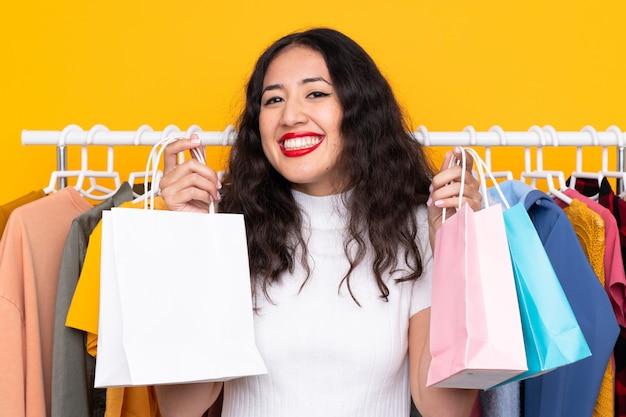 Mulher em uma loja de roupas e com sacolas de compras
