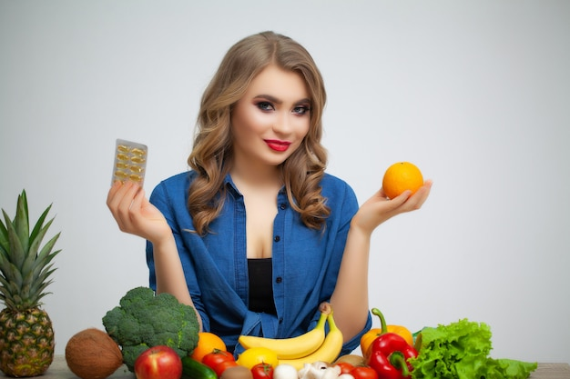 Mulher em uma mesa segurando uma laranja e comprimidos em um fundo de frutas e legumes.