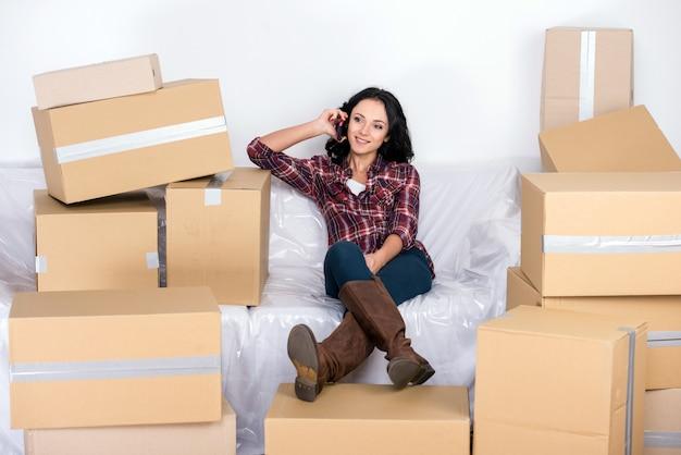 Mulher em uma nova casa com caixas de papelão.