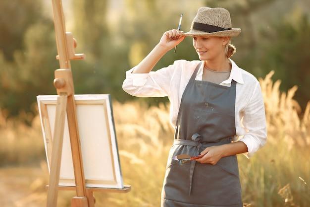 Mulher em uma pintura de avental em um campo