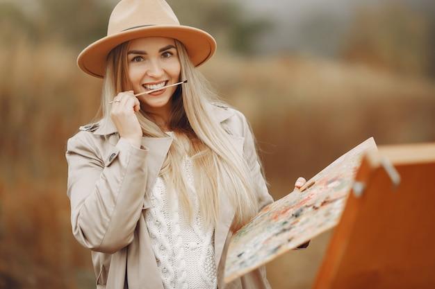 Mulher em uma pintura de casaco marrom em um campo