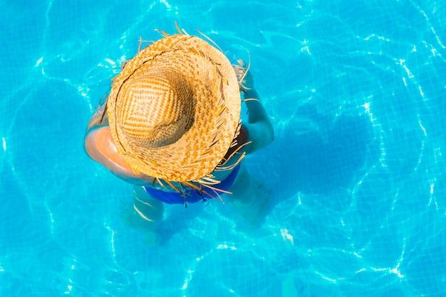 Mulher em uma piscina com chapéu relaxado e descansado.