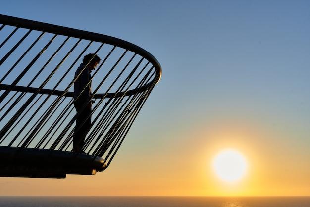 Mulher em uma ponte vendo o nascer do sol sobre o mar