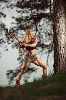 Mulher em uma posição para cortar uma árvore