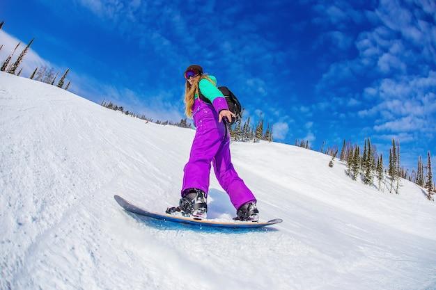 Mulher em uma prancha de snowboard nas montanhas sheregesh.