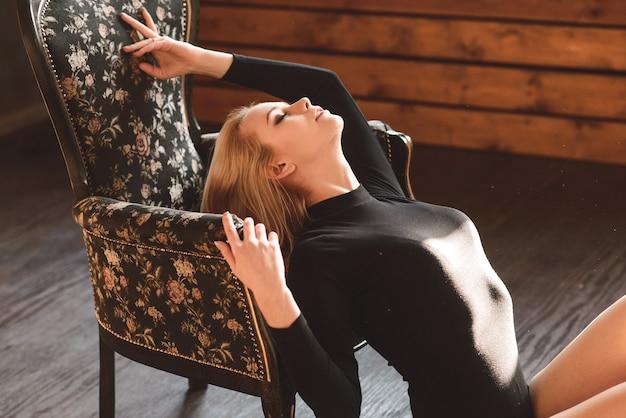 Mulher em uma roupa preta. jovem linda e sensual posando em estúdio