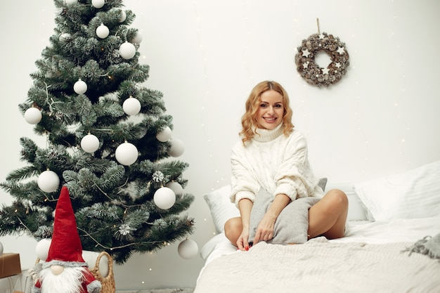 Mulher em uma sala. loira com um suéter branco. senhora perto da árvore de natal.