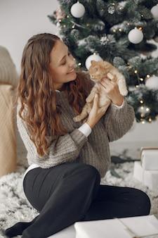 Mulher em uma sala. pessoa com um suéter cinza. senhora com gatinho.