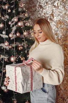 Mulher em uma sala. rapariga com uma camisola branca. senhora perto da árvore de natal.