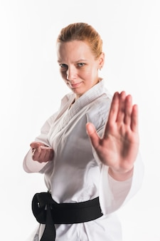 Mulher em uniforme branco de karatê posando
