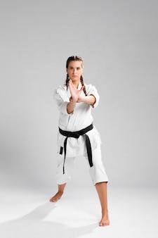 Mulher em uniforme de artes marciais, exercitando karatê