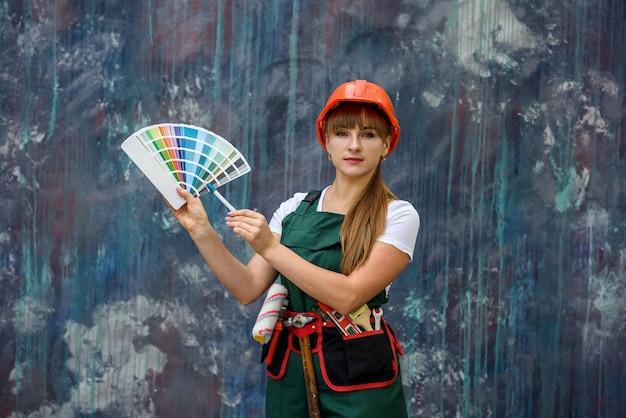 Mulher em uniforme de proteção com amostra de cor posando