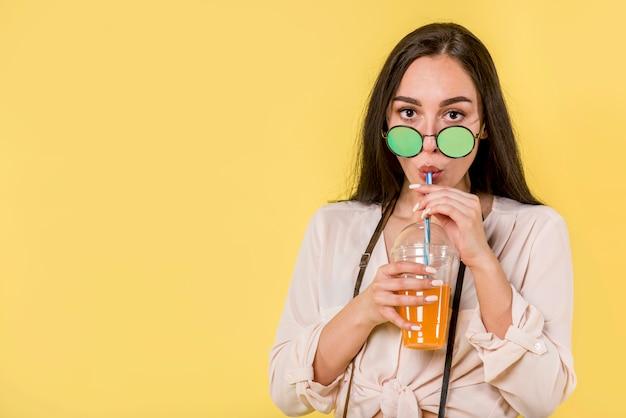 Mulher, em, verde, óculos de sol, com, suco