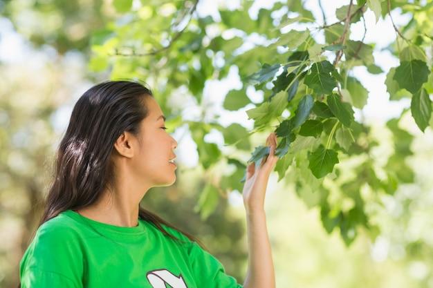 Mulher, em, verde, reciclagem, t-shirt, cheirando, folhas, parque