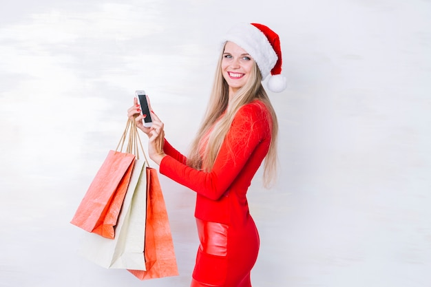 Mulher, em, vermelho, com, bolsas para compras, e, telefone