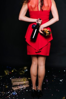 Mulher, em, vermelho, garrafa segurando, com, caixa presente, costas