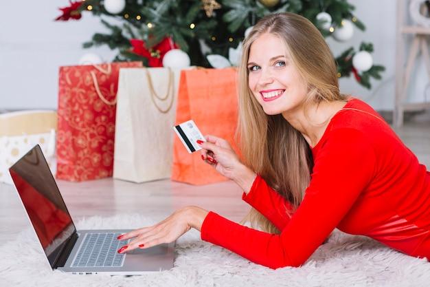 Mulher, em, vermelho, mentindo chão, com, laptop, e, cartão