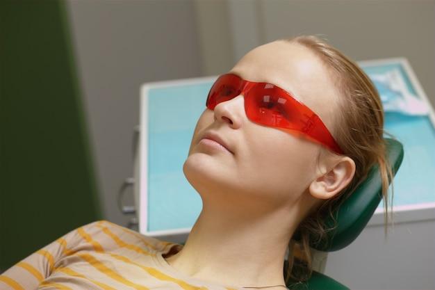 Mulher, em, vermelho, óculos de segurança, em, dental, escritório