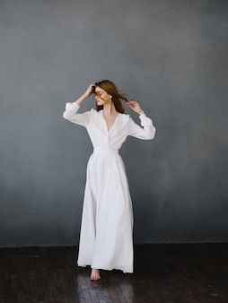 Mulher em vestido branco dança performance